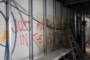Graffiti syns på en tegelvägg som håller på och byggs om.