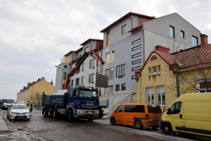 En liten lastbil står vid en byggarbetsplats i ett flervåningshus.