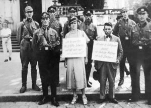 SA- ja SS-miehet nöyryyttävät julkisesti juutalaismiestä ja saksalaisnaista, jotka on tavattu yhdessä