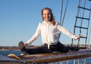 Emma Dönnes gör spagat på en segelskutas bom.