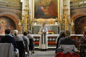 En präst talar framför altaret i Åbo domkyrka där en kvällsmässa ordnades för att minnas offren i fredagens attack i Åbo.
