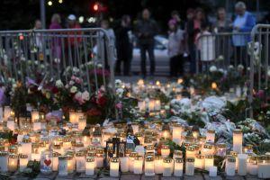 Sörjande människor tittar på ljus och blommor som lämnats på Salutorget i Åbo på lördagskvällen den 19.8.2017.