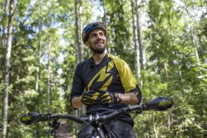 Matti Lehikoinen istuu pyöränsä päällä hymyillen.