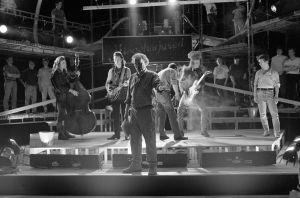 Ohjaaja, käsikirjoittaja Neil Hardwick ja rockyhtyettä esittävät muusikot televisiosarja Pakanamaan kartan kuvauksissa Suomessa vuonna 1990.