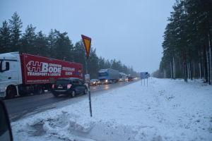 Fordon står i en kö på en snöig väg.