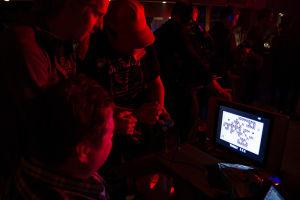 Kolme miestä pelaa Commodore 64:llä.
