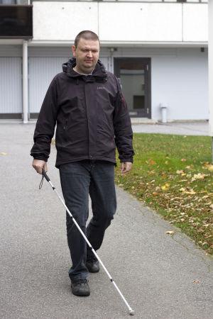 Andreas Kanto går mot kameran. Vi är utomhus och i bakgrunden syns ett höghus. Han går med vit käpp.