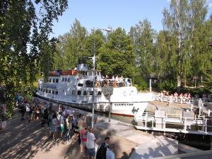 Sisävesimatkustajalaiva M/S Suometar kanavan suluissa, useita ihmisiä kanavanrannassa katsomassa.