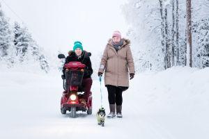 Katri Blomqvist kävelee Mano-koiran kanssa ja Erno Blomqvist ajaa vieressä sähkömopolla.