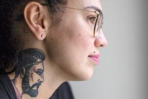 Lähikuva Natalia Tolmatsovan kaulalle tatuoidusta mieshahmosta.