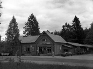 Mustavalkoisessa arkistokuvassa harjakattoinen vanha myymälä, teksti Pulsan puoti