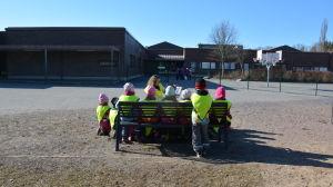 Barn samlade kring lärare som läser utomhus.