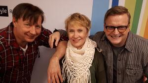 Pasi Hiihtola, Tuija Rantalainen ja Mikko Harjunpää seisovat Radio Suomen tunnuksen edessä