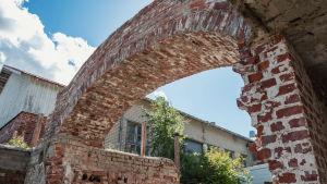 Alakulmasta kuvattu kuva punatiilisestä holvikaaresta, taustalla vaalea rakennus