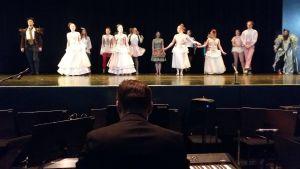 Ungdomar på en scen klädda i fantasifulla klänningar med krusiduller. Nedanför scenen sitter kapellmästaren vid pianot.