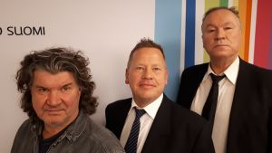 Tero Liete, Lasse Wikman ja Ilkka Vainio seisovat Radio Suomen tunnuksen edessä