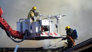 Brandmän släcker takbrand.