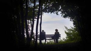 Ett par sitter långt ifrån varandra på en parkbänk.