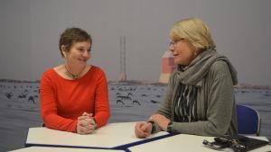 Maria Ekman-Ekebom och Kristiina Koli sittandes vid ett bord.