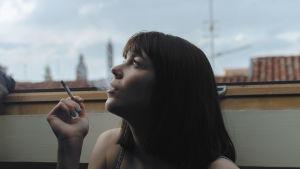 Kvinna röker på takterass