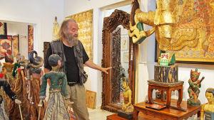 en äldre man står och presenterar sin konstutställning