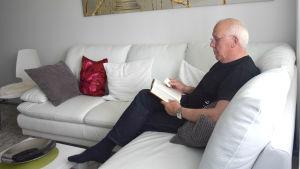 En man sitter i en vit lädersoffa och läser en bok.