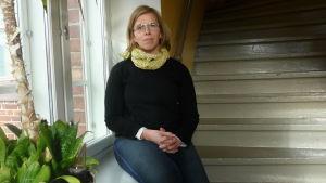 Forskaren Mia Heikkilä sitter vid ett fönster