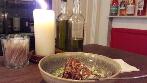 En dessertportion, ett levande ljus, ett par olivoljeflaskor.