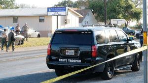 Polisbil och poliser innanför avspärrningen vid brottsplatsen i Sutherland Springs i Texas,