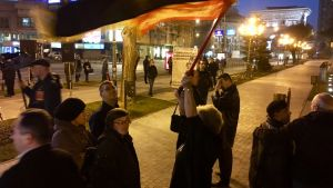 En äldre dam med en stor makedonsk flagga under en liten demonstration i Skopje