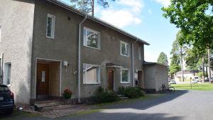 Bild på ett rappat hus i två våningar. I bakgrunden träd och andra hus. En cykel står lutad mot väggen.