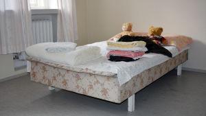 Säng med tecken, handdukar och ett par nallar på.