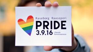 Någon håller i ett vykort där det står Raseborg Pride.