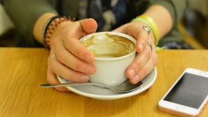 Två händer håller i en kaffekopp med mjölkskum. En telefon ligger bredvid på bordet.