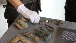 Arkeolog med vita vantar lägger fram fynd på en bordsyta.