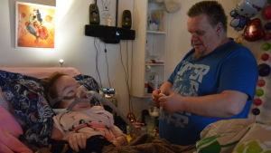 Peter Wiksjö hjälper dottern Jennifer med en mask hon behöver för att kunna andas lättare då hon sover.