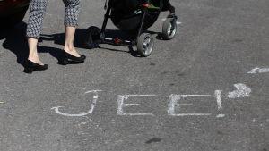 kvinna med barnvagn och text skriven på marken