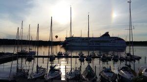 Passagerarfartyget M/S Baltic Princess passerar Airisto Segelsällskaps klubbhamn på Backholmen i Åbo, med segelbåtar i hamnen och en luftballong i bakgrunden.
