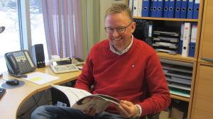 David Strömbäck sitter vid skrivbord bläddrar i katalog