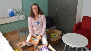 Kvinna sitter med en bok i handen. Öppnade lådor fulla med böcker står omkring henne.