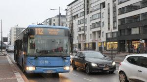 Buss 112 till mattby stannar på hållplats vid biskopsbron i mattby, en våt decemberdag, i bakgrunden höghus