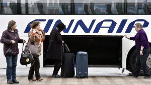 Passagerare får sitt bagage ur babageutrymmet på Finnairs flygbuss.