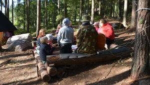 Barn och personal sitter vid en lägerplats.