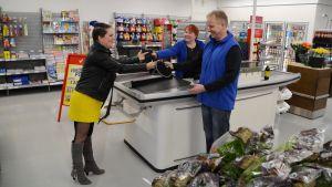 Barbro Lundström från Hindhår byaförening överräcker två mössor åt de nya butiksägarna Aulis och Mira Konttinen i Hindhår nyöppnade bybutik 05.04.18