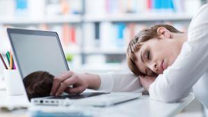 en ung kvinna har somnat vid sin dator.