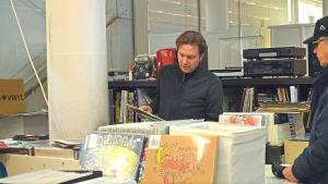 Mikael Winogradow visar vinylskivor som han håller i åt en kund.