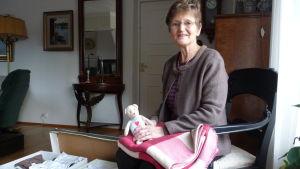 Carola Tigerstedt sitter på stol med rosa babyfilt och mjukisdjur i famnen. Vid fötterna två mammalådor hom själv packat fulla med babykläder.