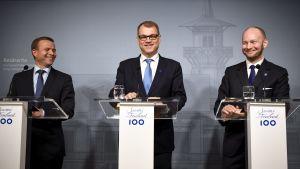 Petteri Orpo, Juha Sipilä och Sampo Terho står bakom varsitt podium.