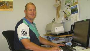 En man sitter vid en dator och ler. I bakgrunden syns en utskrivare och en annan dator samt papper på en anslagstavla med många papper. Mannen är klädd i t-tröja.