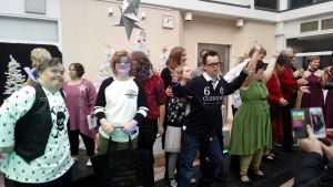 Flera personer står på en catwalk och tackar publiken efter en modevisning.